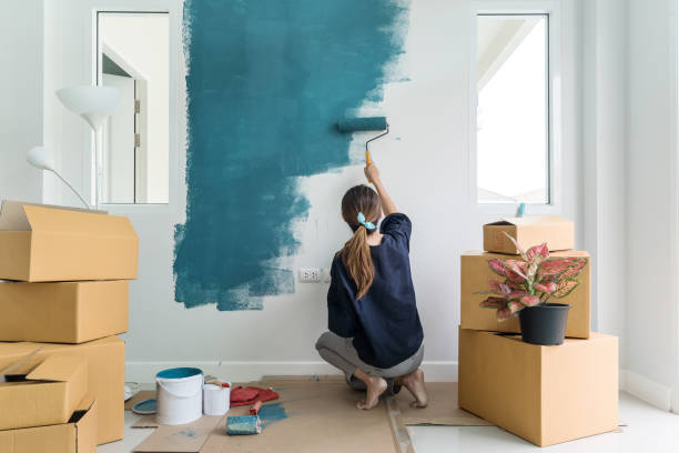 Young asian happy woman painting interior wall stock photo