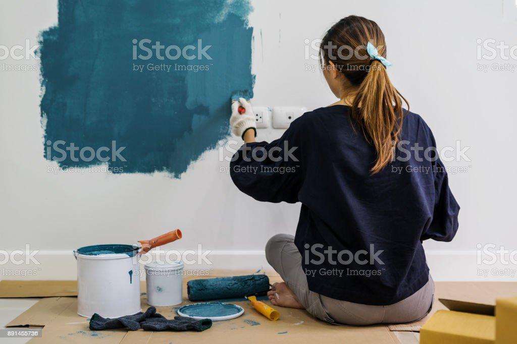Junge Asiatin glücklich Malerei Innenwand mit Farbroller in neues Haus – Foto