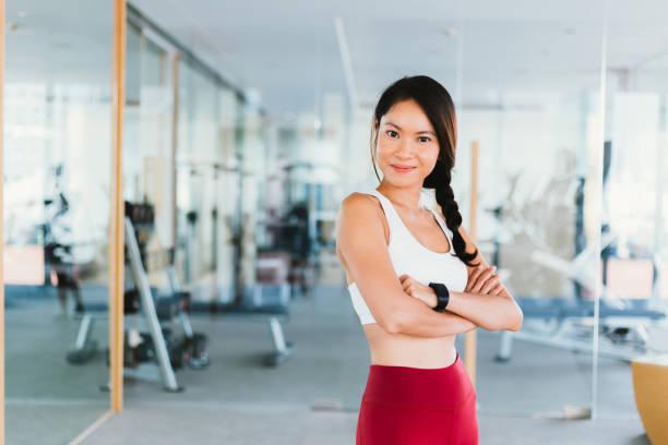Junge asiatische gesunde und fröhlich schöne Fitness Sportlerin in Sportbekleidung mit Waffen gekreuzt und Blick auf die Kamera Pose im Fitnessstudio. – Foto