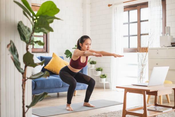 joven asiática mujer sana entrenamiento en casa, ejercicio, ajuste, hacer yoga, concepto de fitness en el hogar - agacharse fotografías e imágenes de stock