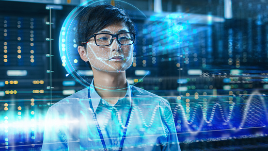 istock Young Asian IT Engineer Identified by Biometric Facial Recognition Scanning Process in Data Center Server Room. Futuristic Concept: Projector Identifies Individual by Illuminating Face by Lines. 1159763170
