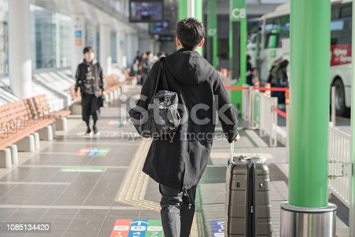 Young asian japanese man travel by public transportation and waiting for bus in bus station japan