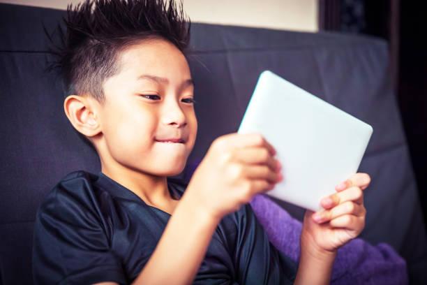 デジタル タブレットで遊ぶ若いアジアの子供 - 小学校低学年 ストックフォトと画像
