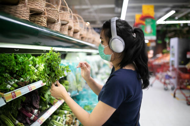 Young asian lady in medical face mask shopping in a supermarket stock photo