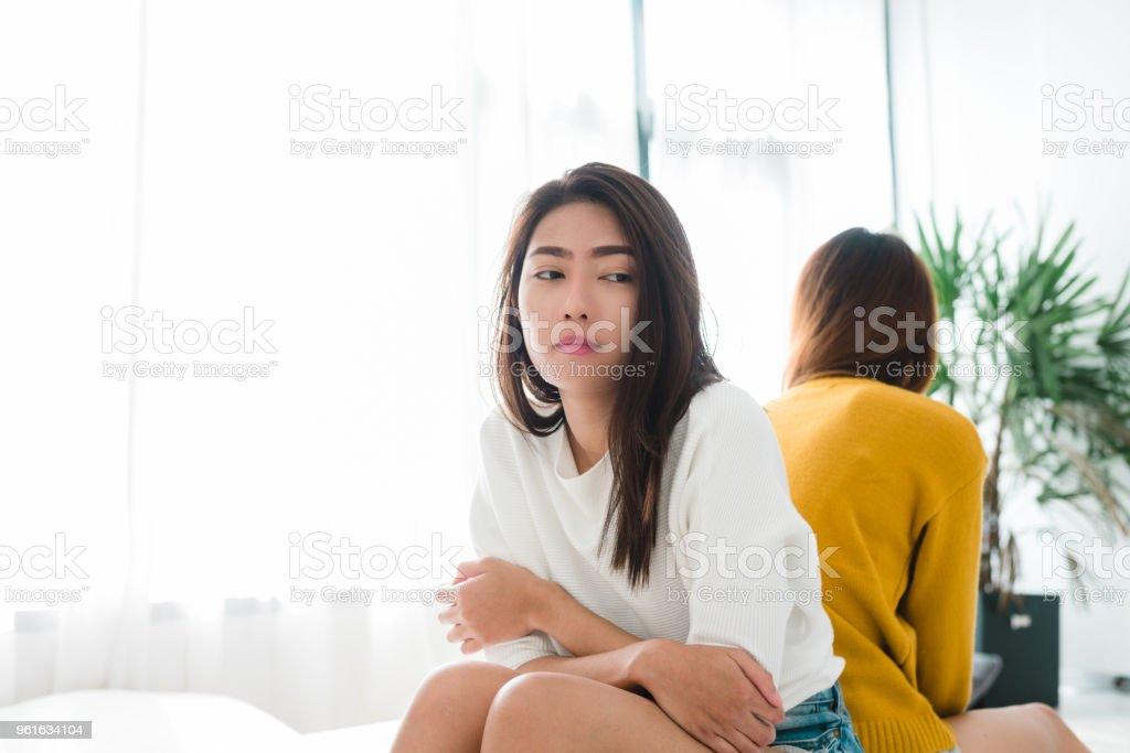 Young Asian lesbian couple argue and turn their back to each other in the period of sad in the bedroom. LGBT couple sulky to another in the bedroom with a sad mood. LGBT lover emotion concept. Young Asian lesbian couple argue and turn their back to each other in the period of sad in the bedroom. LGBT couple sulky to another in the bedroom with a sad mood. LGBT lover emotion concept. Adult Stock Photo