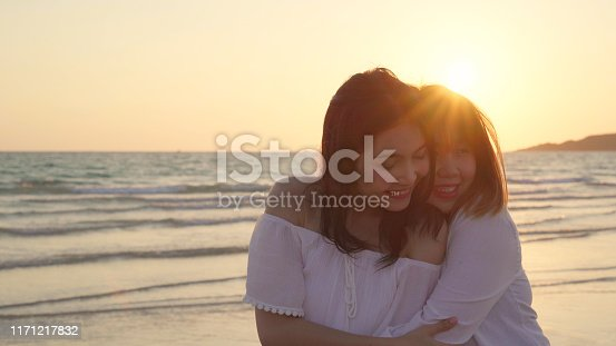 Young Asian lesbian couple kissing near beach. Beautiful women lgbt couple happy relax enjoy love and romantic moment when sunset in evening. Lifestyle lesbian couple travel on beach concept.