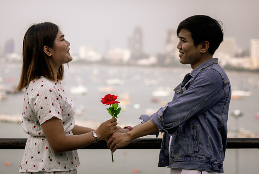 Young Asian love couple holding a rose standing at city viewpoint with resting together
