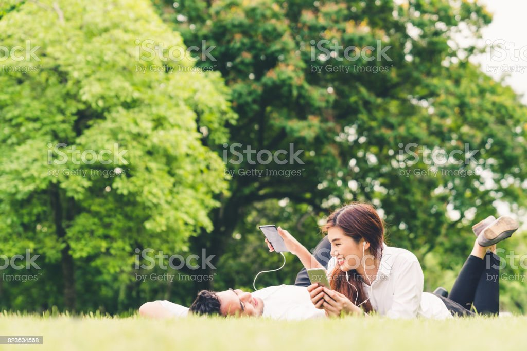 Young Asian Lovely Couple Or College Students Listening To Music