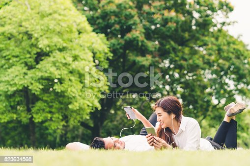 istock Young Asian lovely couple or college students listening to music together in the garden, with copy space. Leisure activity, Love relationship, wedding, or relaxing casual lifestyle concept 823634568