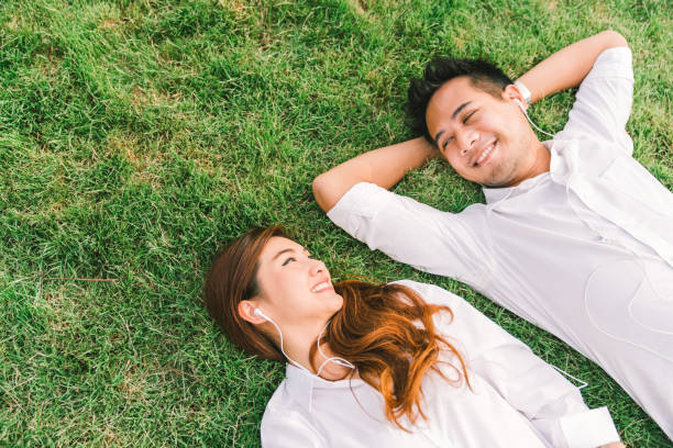 Young Asian lovely couple or college students lying down on the grass together, listening to music, top view with copy space. Love, relationship, wedding, or relaxing casual lifestyle concept stock photo