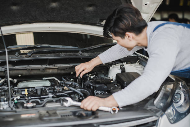 Young Asian machine technicians are analyzing symptoms of broken car at service center repair stock photo