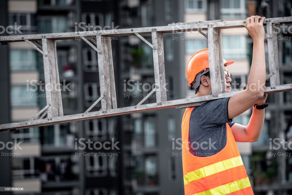 Young Asian maintenance worker with orange safety helmet and vest carrying aluminium step ladder at construction site. Civil engineering, Architecture builder and building service concepts stock photo