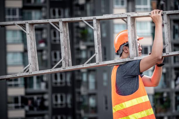 jonge aziatische onderhoud werknemer met oranje veiligheidshelm en vest uitvoering aluminium stap ladder op de bouwplaats. civiele techniek, het platform builder en het opbouwen van serviceconcepten - ladder stockfoto's en -beelden
