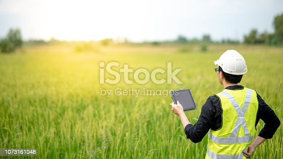 istock Young Asian male agronomist or agricultural engineer observing green rice field with digital tablet and pen for the agronomy research. Agriculture and technology concepts 1073161048