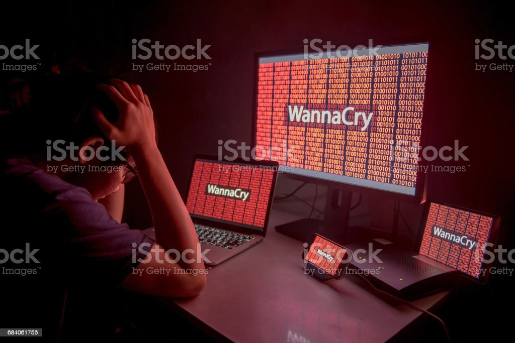 Young Asian male confused and headache by WannaCry ransomware attack stock photo
