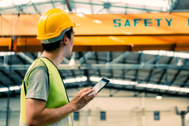 unga asiatiska manliga fabriks arbetare med hjälp av en digital tablett - arbetssäkerhet bildbanksfoton och bilder