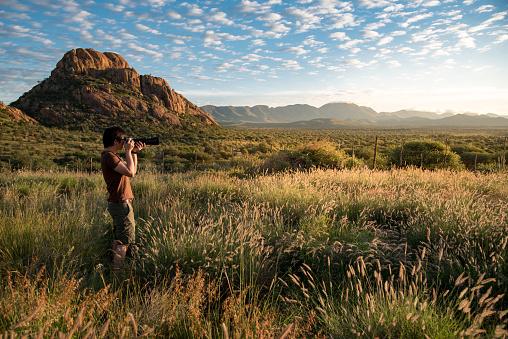 Young Asian male photographer taking photo of beautiful sunrise in savannah woodland, Namibia