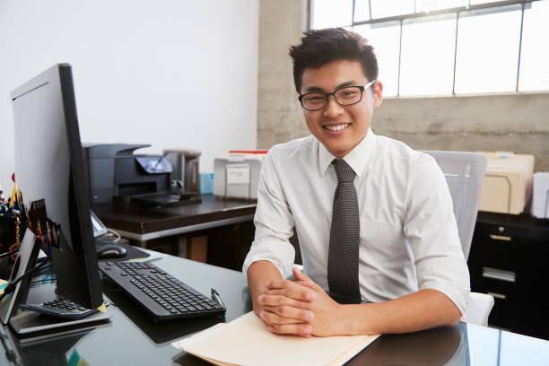 Young Asian male professional at desk smiling to camera Young Asian male professional at desk smiling to camera korean ethnicity stock pictures, royalty-free photos & images