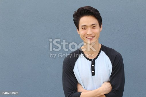 689644378istockphoto Young Asian male smiling and laughing with arms crossed 846731528