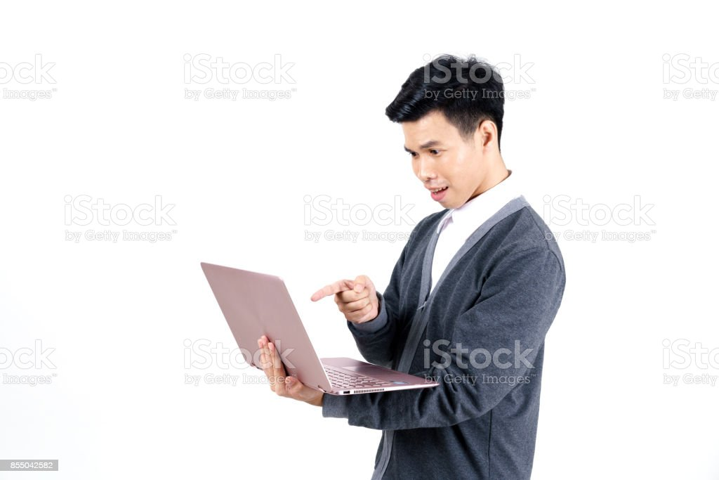 Young Asian male student in grey jacket pointing his finger at laptop isolated on white background stock photo