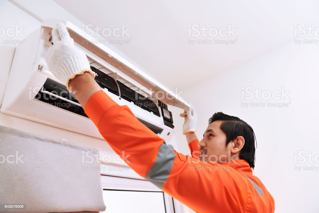 Young asian male technician repairing air conditioner stock photo