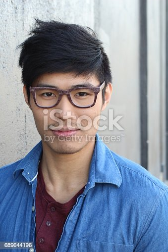 689644378istockphoto Young Asian male with glasses smiling 689644196