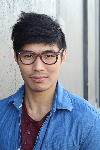 689644378 istock photo Young Asian male with glasses smiling 689644196
