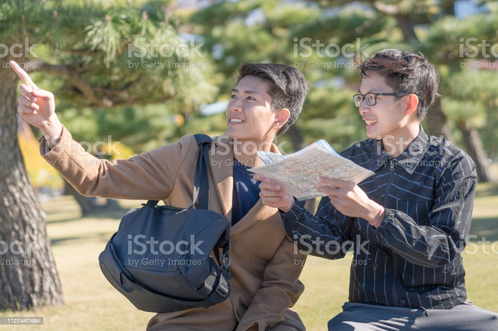 Young asian man and japanese friend looking for travel location using...