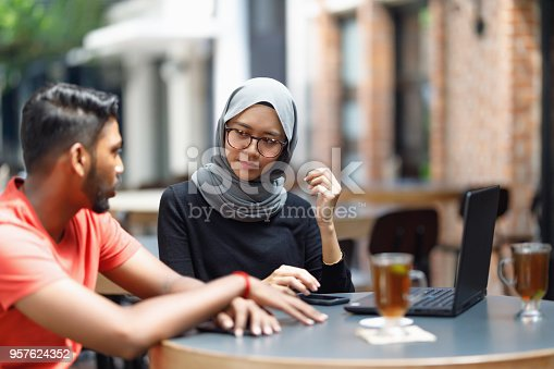 672213742istockphoto Young Asian Man And Muslim Woman Student Working Together At A Cafe 957624352