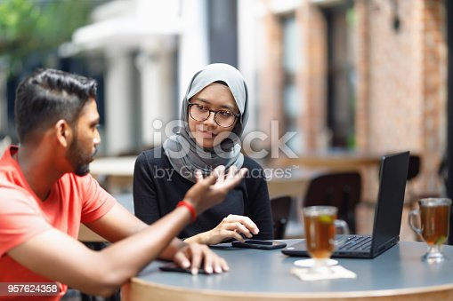 672213742istockphoto Young Asian Man And Muslim Woman Student Working Together At A Cafe 957624358