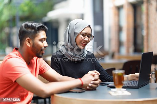 672213742istockphoto Young Asian Man And Muslim Woman Student Working Together At A Cafe 957624368