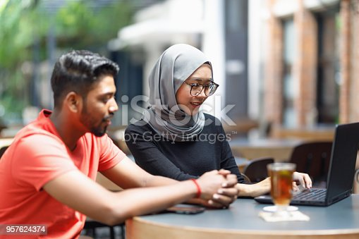 672213742istockphoto Young Asian Man And Muslim Woman Student Working Together At A Cafe 957624374