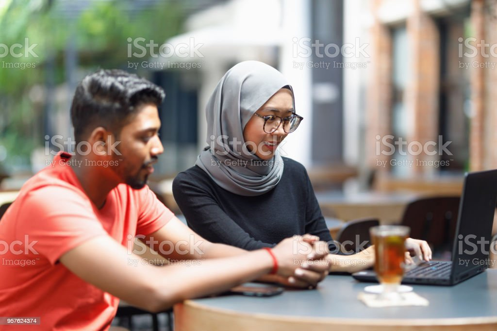 Young Asian Man And Muslim Woman Student Working Together At A Cafe stock photo