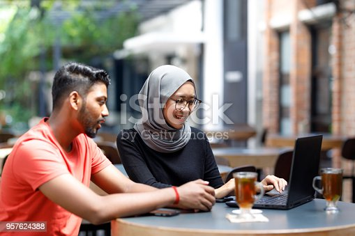 672213742istockphoto Young Asian Man And Muslim Woman Student Working Together At A Cafe 957624388
