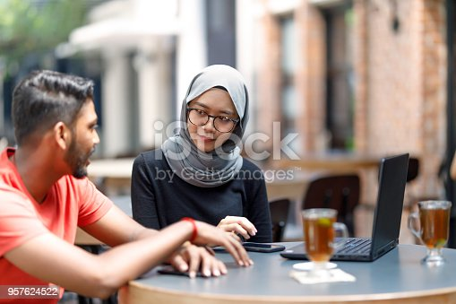 672213742istockphoto Young Asian Man And Muslim Woman Student Working Together At A Cafe 957624522
