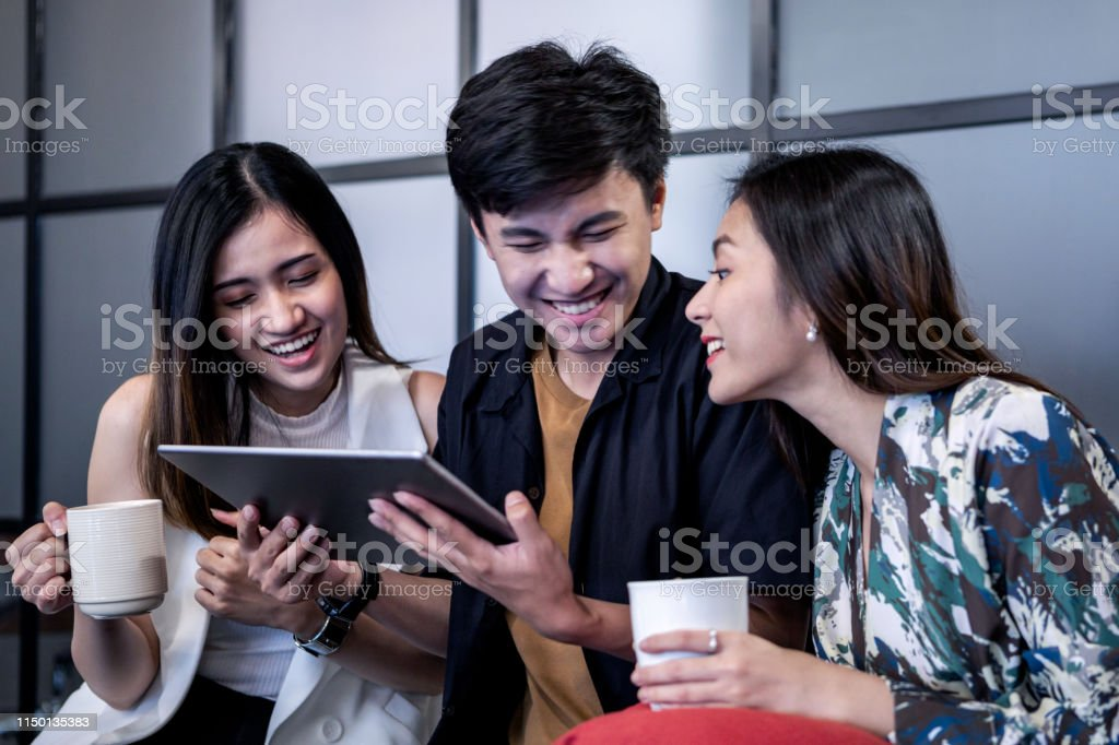 Sitting Together On A Sofa With A Smartphone Laughing And Having Fun