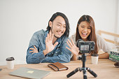 Young Asian man and woman are waving the hand with the camera which standing on the wood table. the couple man and woman sitting in the home and record video clip. blogger and vlog concept