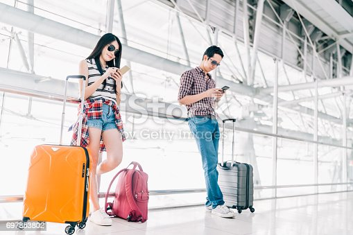 istock Young Asian man and woman using smartphone checking flight or online check-in at airport together, with luggage. Air travel, summer holiday, or mobile phone application technology concept 697853802
