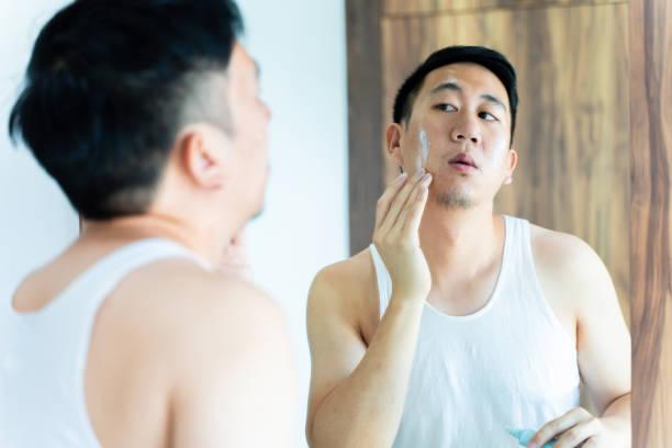 Young Asian man applying skincare cream in bathroom stock photo