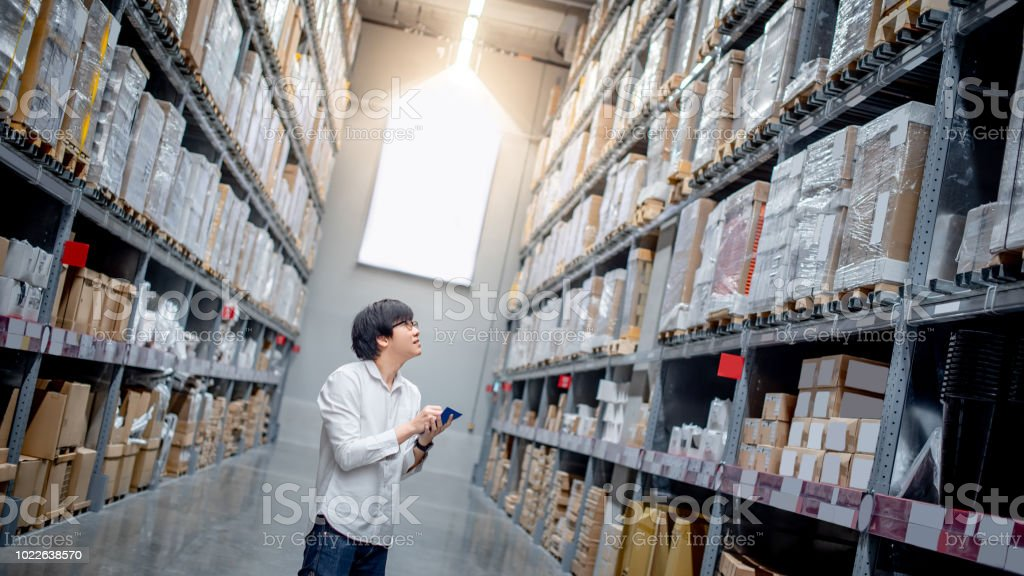 Young Asian man checking the shopping list looking for product in warehouse wholesale, shopping warehousing concept stock photo