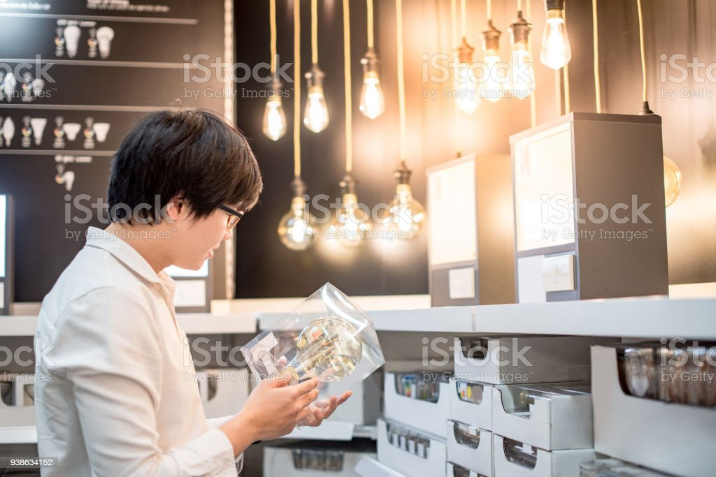 Young Asian man choosing package of electrical light bulb in warehouse stock photo