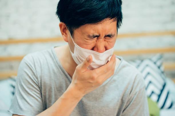 Junge Asiate Husten und Leiden in medizinischer Maske im häuslichen Schlafzimmer-Krankheit und Fieberkonzept. – Foto