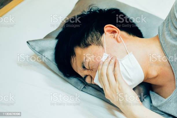 Young asian man coughing and suffering in medical mask inside home picture id1130628396?b=1&k=6&m=1130628396&s=612x612&h=5v rjo9a9hugundf9 rsuysvtreu0mliotbb0aqm ci=