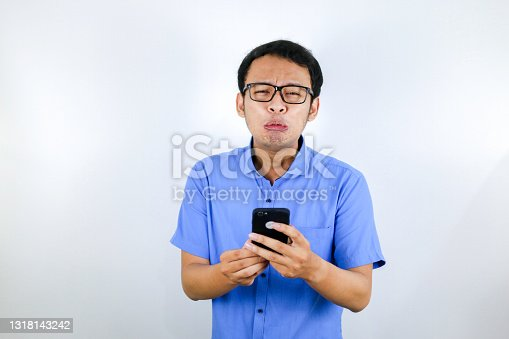 Young Asian man cry and sad when looking and using phone. Indonesia Man wear glasses and blue shirt Isolated blue background.