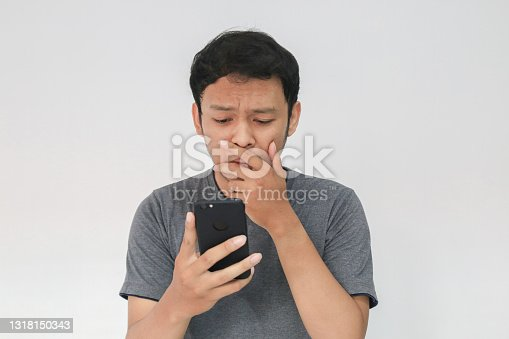 Young Asian man cry and sad when looking on the smartphone. Indonesia Man wear black shirt Isolated grey background.