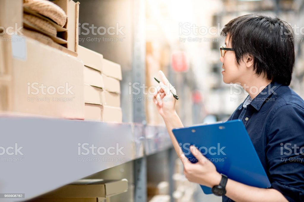Young Asian man doing stocktaking of product in cardboard box on shelves in warehouse by using clipboard and pen stock photo