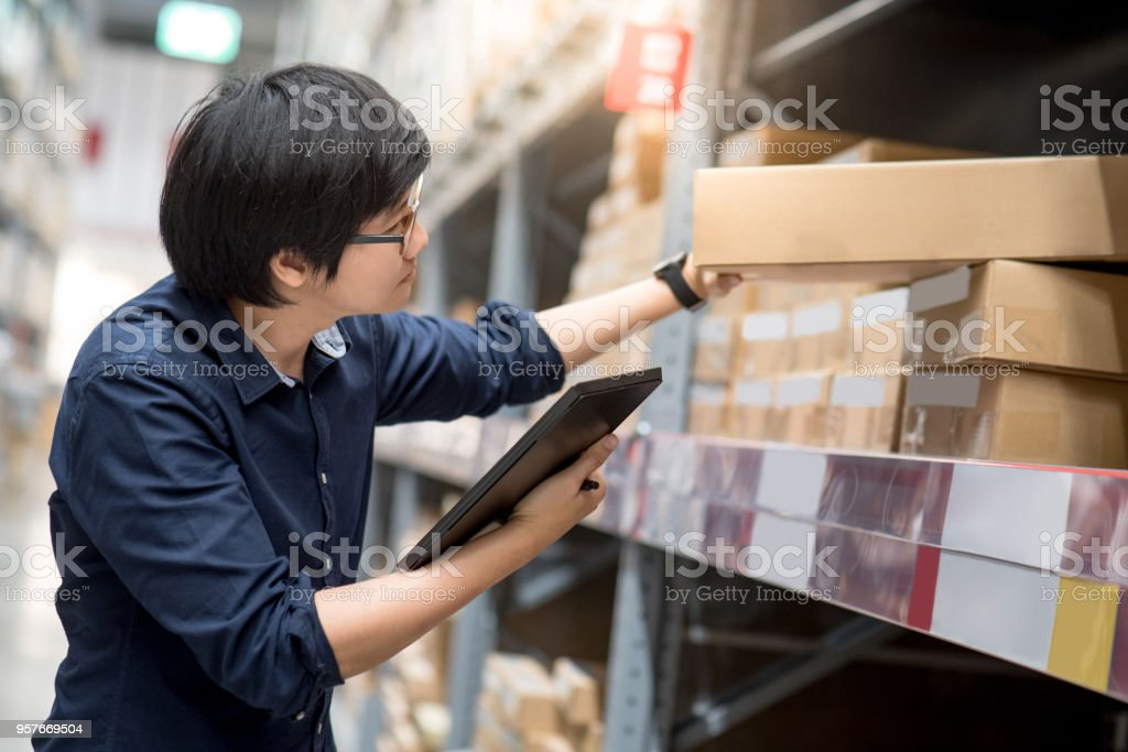 Young Asian man doing stocktaking of product in cardboard box on shelves in warehouse by using digital tablet stock photo