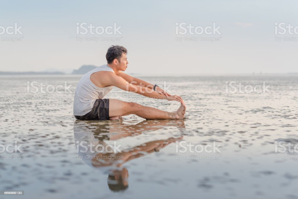 Young asian man doing yoga exercise at sunset beach foto stock royalty-free