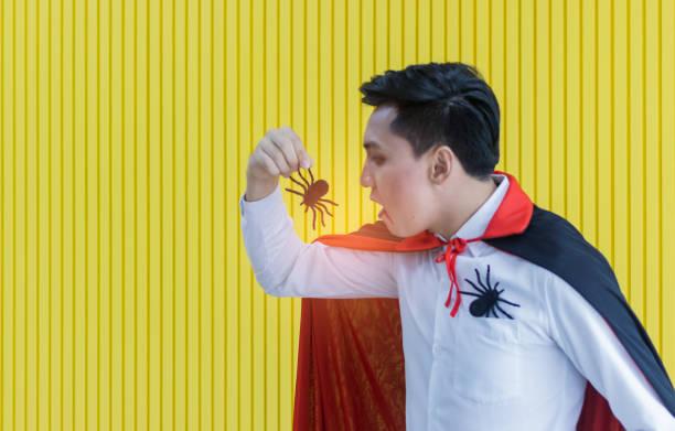 junge asiatische mann in dracula in der halloween-nacht gekleidet und essen eine schwarze spinne, einkonzept, um halloween zu feiern. - dracula schminken stock-fotos und bilder