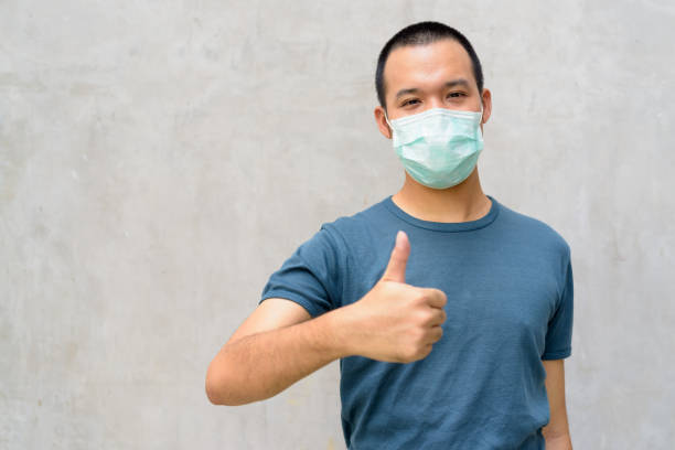 Young Asian man giving thumbs up with mask for protection from corona virus outbreak outdoors stock photo